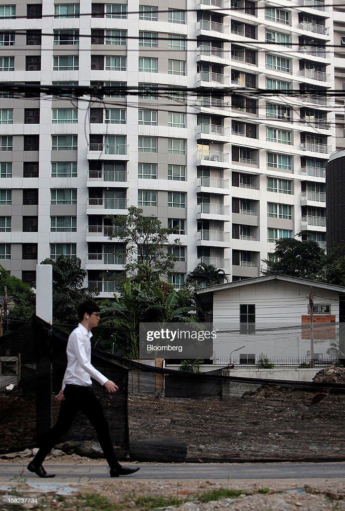 A man walks past a house standing in front of a high rise apartment building in a side street off Langsuan road in Bangkok, Thailand, on Tuesday, Dec. 11, 2012. The Crown Property Bureau owns about 41,300 rai (66 square kilometers) of land across the country, about a fifth of which is in Bangkok, according to Aviruth Wongbuddhapitak, an adviser to the CPB who sits on the board of two of its subsidiaries. Photographer: Dario Pignatelli/Bloomberg via Getty Images