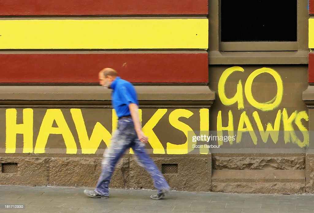 A man walks past a large 'Go Hawks!' sign which is written on the wall of the Arcadia Hotel in South Yarra on September 24, 2013 in Melbourne, Australia. The Hawthorn Hawks play the Fremantle Dockers this Saturday in this year's 2013 AFL Grand Final.
