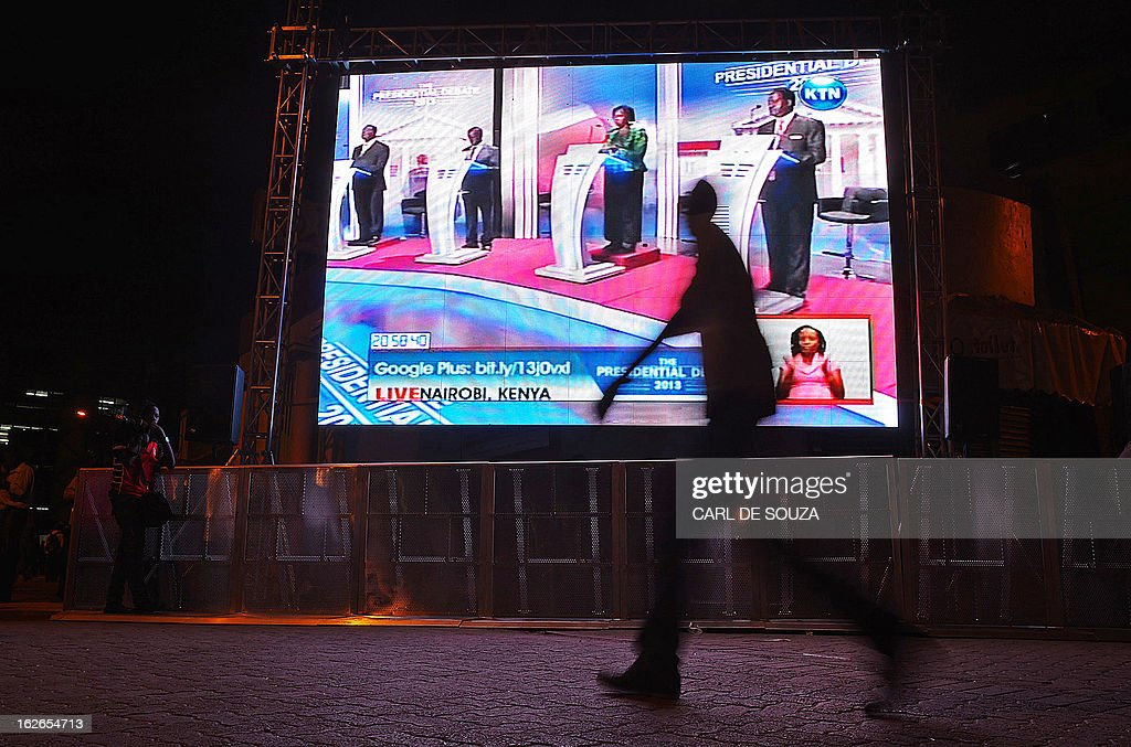 A man walks past a large screen in Central Nairobi broadcasting the last televised debate for the 2013 Kenya elections on February 25, 2013. Kenyans will vote for a new leader on March 4, 2013. AFP PHOTO/Carl de Souza