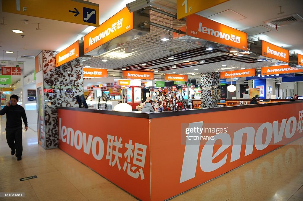 A man walks past a Lenovo shop in a computer mall in Beijing on November 3 2011 The founder of Chinese computer giant Lenovo Group Liu Chuanzhi has...