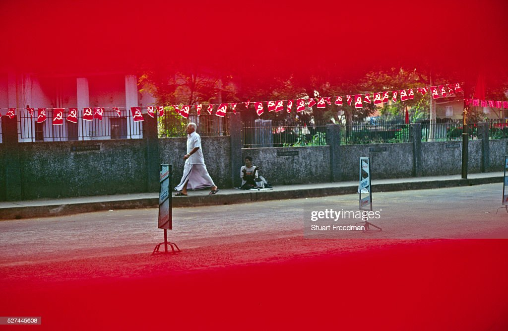 A man walks past a leperous beggar as seen through a Communist Party banner in Calicut India Since it's election in 1957 Kerala's Communist Party has...