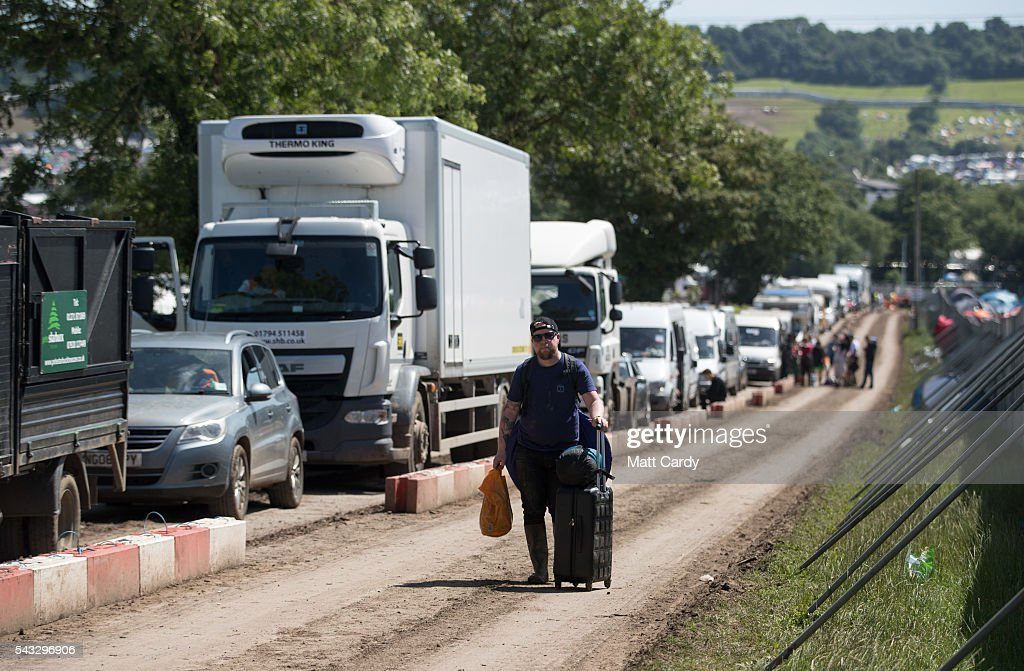 A man walks past a line of vehicles waiting to leave the Glastonbury Festival 2016 at Worthy Farm, Pilton on June 26, 2016 near Glastonbury, England. The Festival, which Michael Eavis started in 1970 when several hundred hippies paid just £1, now attracts more than 175,000 people.