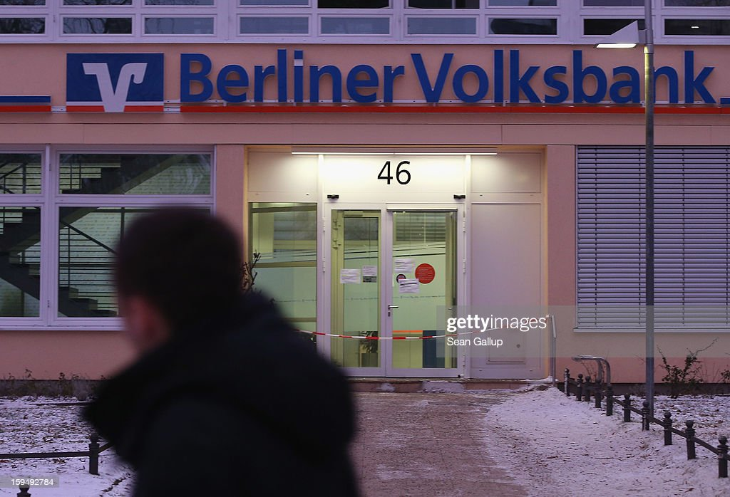 A man walks past a locked Steglitz district branch of Berliner Volksbank following a robbery of the bank that likely occured in the early morning hours on January 14, 2013 in Berlin, Germany. According to police the robbers dug a 30 meter long tunnel from a nearby underground parking garage to access the vault of the bank and made off with the contents.