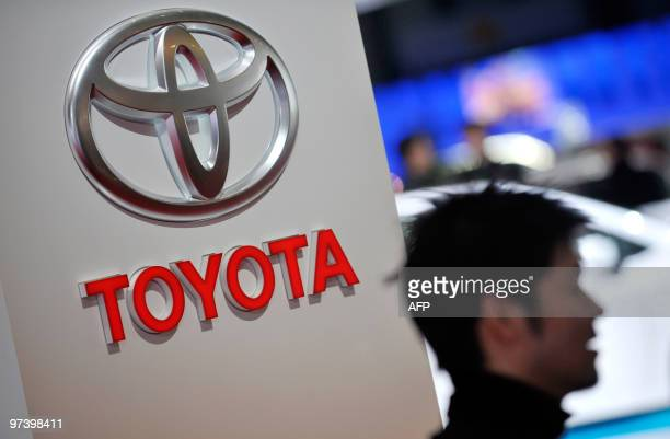 A man walks past a logo of Japanese car manufacturer Toyota at the 80th Geneva International Motor Show at Palexpo in Geneva on March 3 2010 Global...