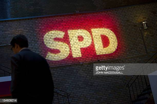 A man walks past a logo of the Social Democratic Party outside the venue of their annual convention in Berlin December 5 2011 AFP PHOTO / JOHN...