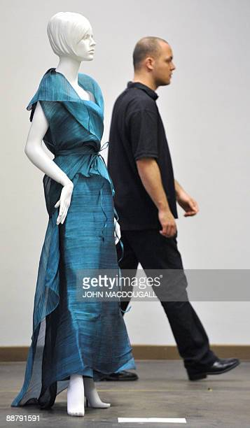 A man walks past a mannequin wearing fashion made of banana fibre mixed with indigenous Filipino fabric by Dita Sandico Ong of the Philippines on...