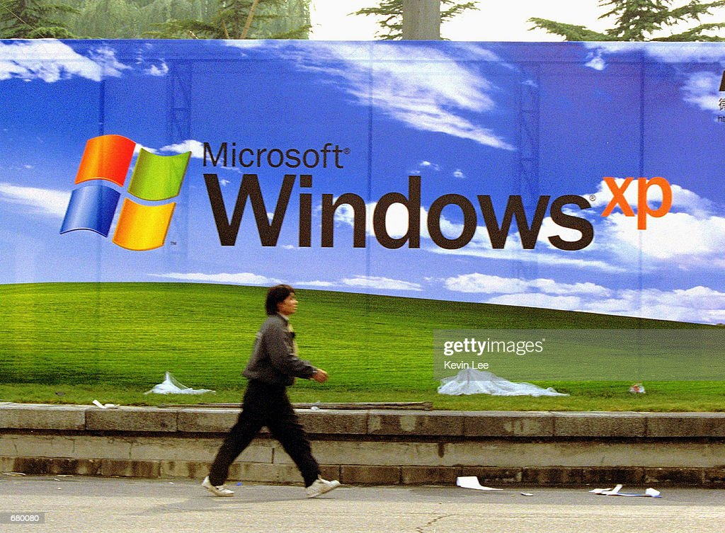 A man walks past a Microsoft billboard featuring its latest software, Windows XP, at the entrance of a conference center November 7, 2001 in Beijing. Microsoft will hold a press conference on November 9 in Beijing to introduce the Chinese version of the software.