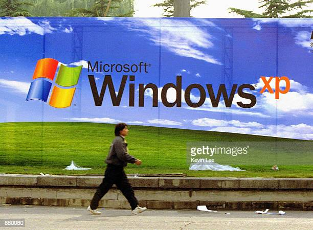 A man walks past a Microsoft billboard featuring its latest software Windows XP at the entrance of a conference center November 7 2001 in Beijing...