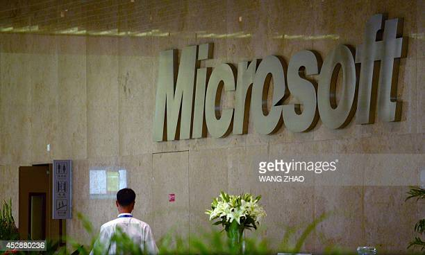 A man walks past a Microsoft logo at a buliding in Beijing on July 29 2014 China is investigating Microsoft for allegedly operating a monopoly in its...