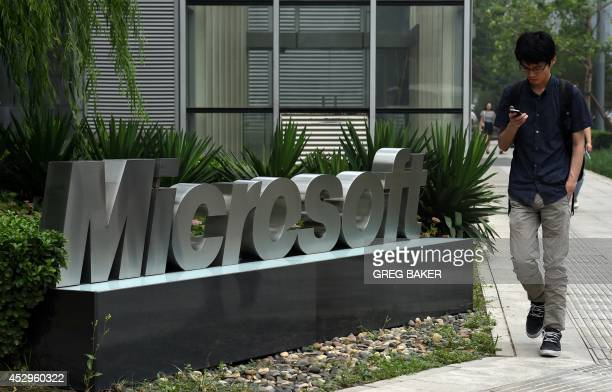 A man walks past a Microsoft sign outside a Microsoft office building in Beijing on July 31 2014 Microsoft said July 30 it seeks to comply with...