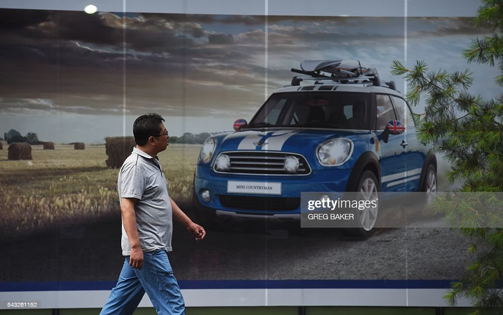 A man walks past a Mini showroom in Beijing on June 27, 2016. Britain's vote to leave the European Union has added new uncertainties to the world economy at a time when downward pressures on China's economy are mounting, Premier Li Keqiang said on June 27 at a World Economic Forum meeting in the Chinese city of Tianjin. / AFP / GREG