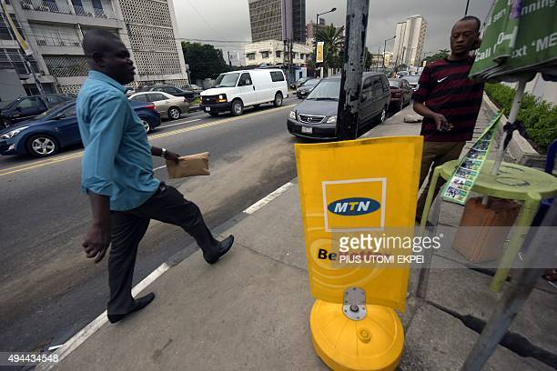 A man walks past a MTN notice board in Lagos on October 27 2015 Nigeria's telecommunications regulator has fined South African mobile giant MTN $52...
