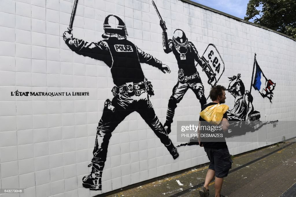 A man walks past a mural by French artist Goin on June 27, 2016 in Grenoble, southeastern France. Mayor of Grenoble Eric Piolle (EELV) Monday invoked the freedom of expression after the controversy surrounding an urban art work deemed 'anti-police,' and created as part of a festival sponsored by the municipality. / AFP / PHILIPPE