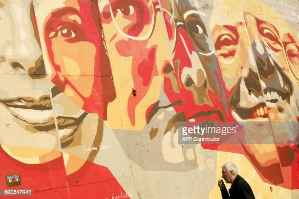 A man walks past a mural depicting Italian singer Ornella Vanoni Italian singer Enzo Jannacci and Italian 1997 Nobel Prize in Literature Dario Fo on...