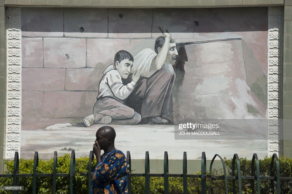 A man walks past a mural depicting Palestinian Jamal al-Dura and his son Mohammed, allegedly caught in crossfire between Israeli forces and Palestinian police, moments before Mohammed was killed, can be seen at the Place de l'Enfant Martyr de Palestine (square of the Palestinian martyr child) in Bamako, on March 6, 2013. The monument commemorates the September 30, 2000 event, which has since launched a controversy, with some commentators alleging that the incident had been entirely staged.
