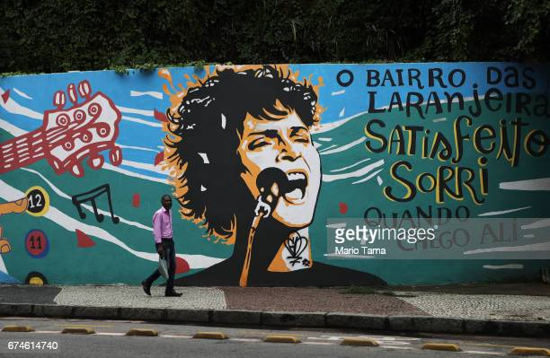 A man walks past a mural during a nationwide general strike on April 28 2017 in Rio de Janeiro Brazil The general strike was conducted in cities...