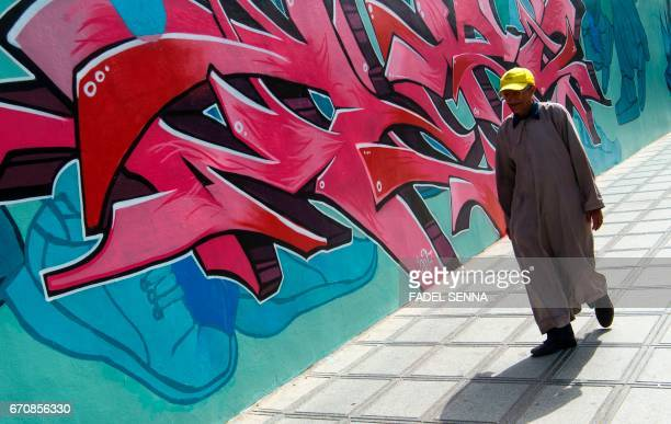 A man walks past a mural during the 'Jidar' street art festival in the capital Rabat on April 20 2017 / AFP PHOTO / FADEL SENNA