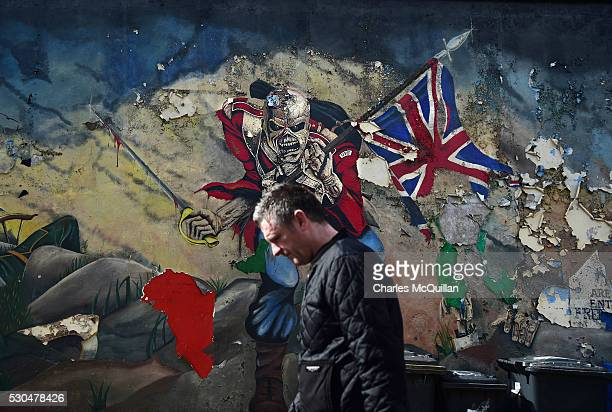 A man walks past a mural marking unionist territory on May 4 2016 in Londonderry Northern Ireland The city of Londonderry is situated on the border...