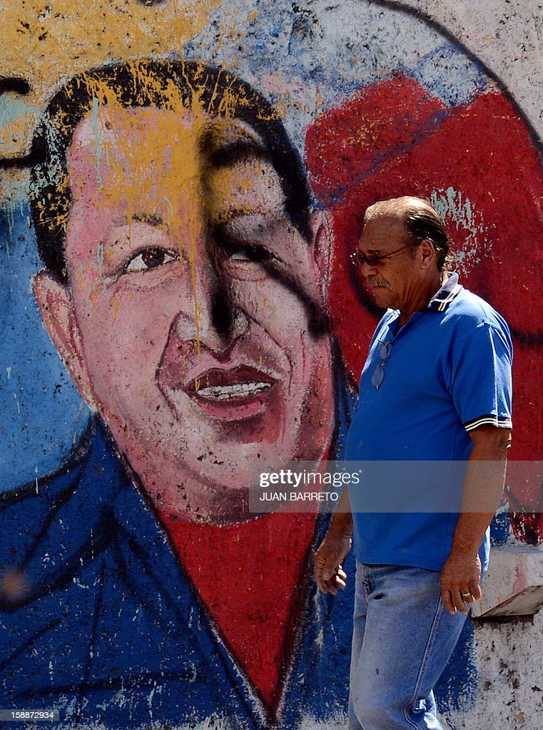 A man walks past a mural of Venezuelan President Hugo Chavez in Caracas, on January 2, 2013. Chavez is conscious and fully aware of how 'complex' his condition remains three weeks after difficult cancer surgery in Havana, the Venezuelan president's handpicked successor, Vice President Nicolas Maduro, said Tuesday. Chavez underwent his fourth cancer-related surgery three weeks ago in Havana and has been bed-ridden ever since. AFP PHOTO/JUAN BARRETO