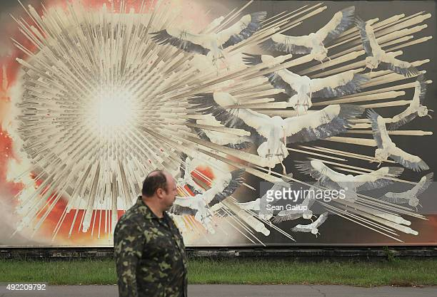 A man walks past a mural on the wall of a museum commemorating the Chernobyl nuclear disaster with an exploding reactor core and images of storks the...