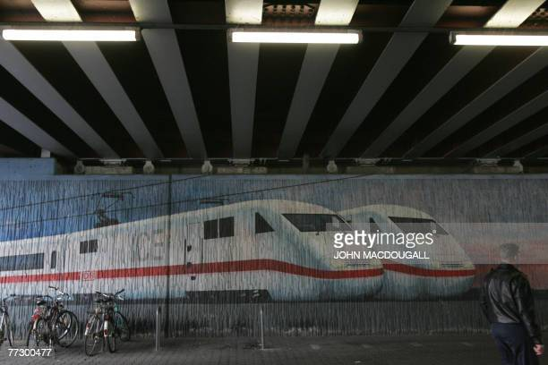 A man walks past a mural painting featuring a Deutsche Bahn ICE train at an SBahn station in Frankfurt 12 October 2007 Up to half of Germany's...