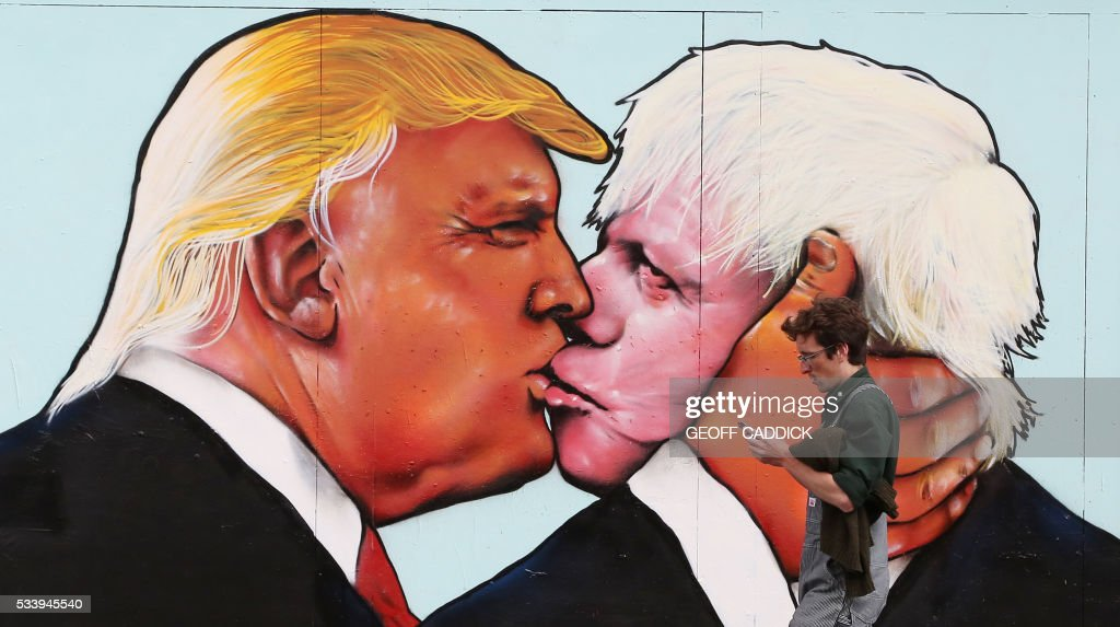 A man walks past a mural showing likely US Republican presidential nominee Donald Trump (L) kissing the Former Mayor of London and Conservative MP, Boris Johnson, on the side of a building in Bristol, south west England on May 24, 2016. The mural in Bristol, southwest England, was commissioned by We Are Europe, a campaign group which wants Britain to remain in the European Union at the June 23 vote. / AFP / GEOFF