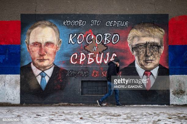 A man walks past a mural vandalized with paint depicting Russian President Vladimir Putin and US President Donald Trump and bearing the Cyrillic...