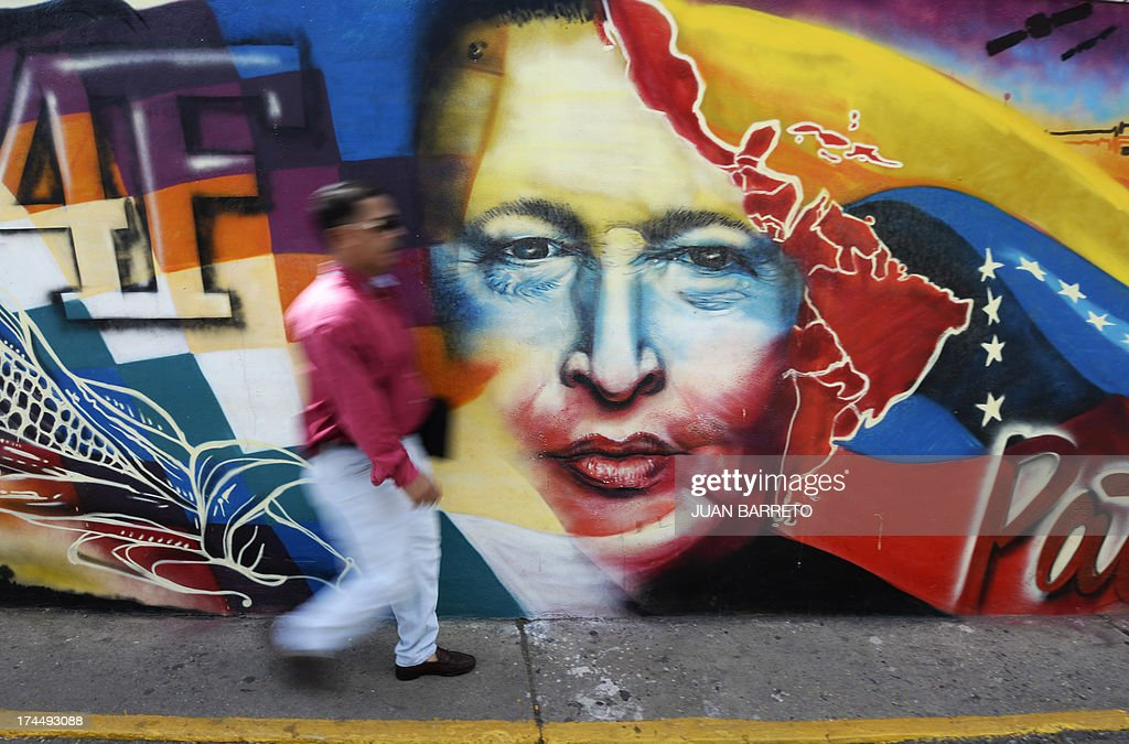 A man walks past a mural with the portrait of former Venezuelan President Hugo Chavez (1954-2013), at '23 de Enero' neighborhood, in Caracas on July 26, 2013. July 28, 2013 marks the first anniversary of Chavez's birth after his death.