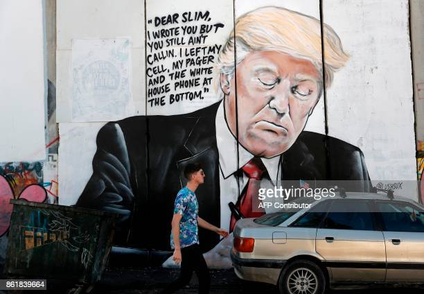 A man walks past a new piece of graffiti depicting US President Donald Trump on the controversial Israeli separation barrier separating the West Bank...
