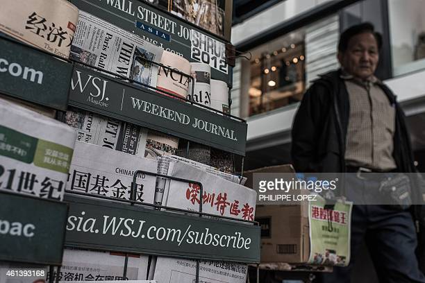 A man walks past a newspaper kiosk in Hong Kong on January 12 2015 Firebomb attacks early on January 12 on the Hong Kong home and office of...