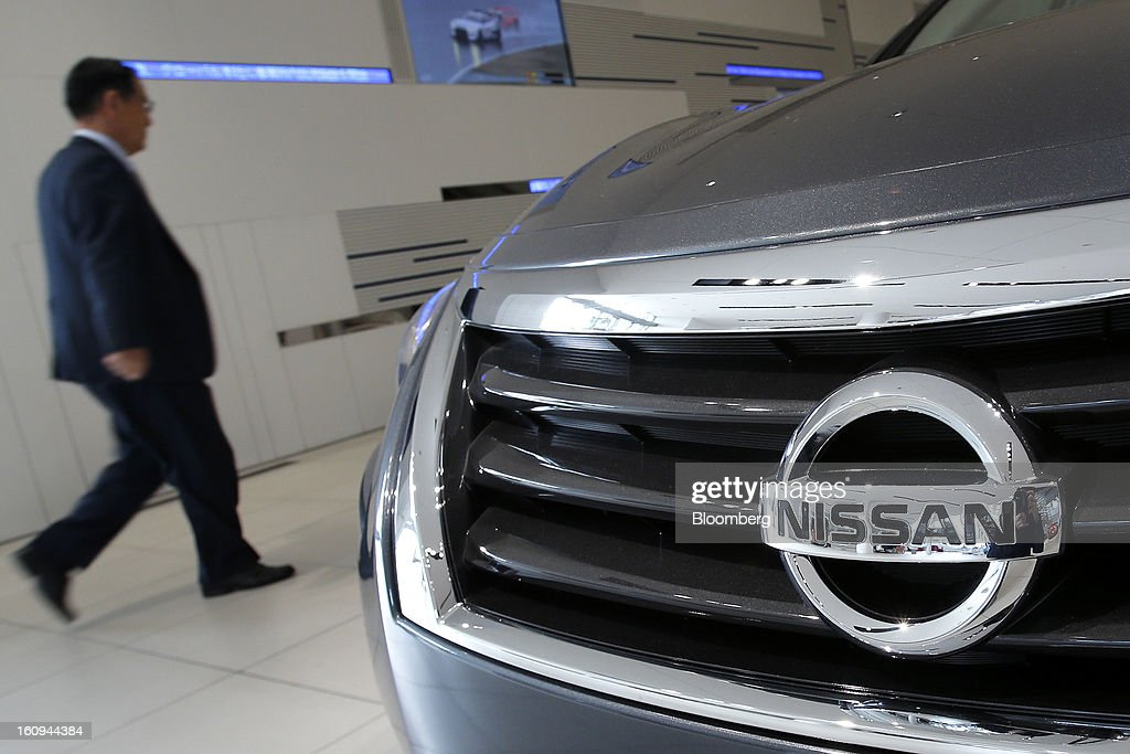 A man walks past a Nissan Motor Co. vehicle displayed at the company's showroom in Yokohama, Kanagawa Prefecture, Japan, on Friday, Feb. 8, 2013. Nissan, Japan's second-biggest carmaker, reported third-quarter profit that fell short of analysts' estimates, after sales tumbled in China and new models trailed competitors in the U.S. Photographer: Kiyoshi Ota/Bloomberg via Getty Images
