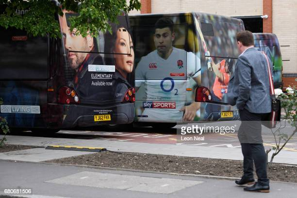 A man walks past a number of heavilybranded buses at the Sky headquarters in Isleworth on May 9 2017 in London England The independent communications...