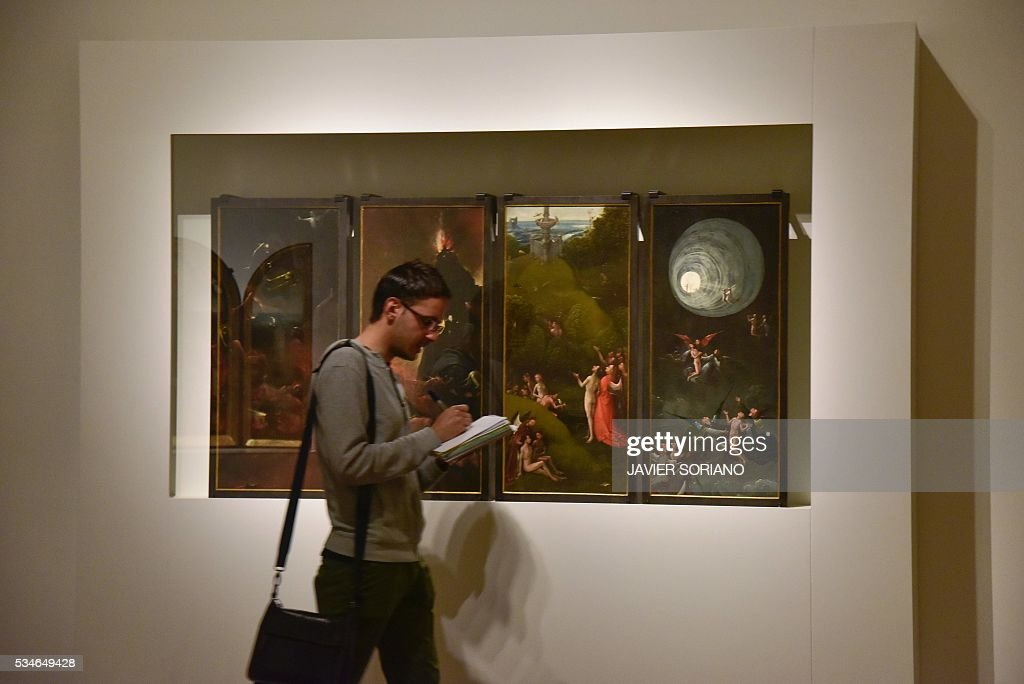 A man walks past a painting by Dutch painter Jheronimus Bosch know as 'El Bosco' during the presentation of the 'The Bosco, The fifth centenary' exhibition at El Prado museum in Madrid on May 27, 2016. / AFP / JAVIER