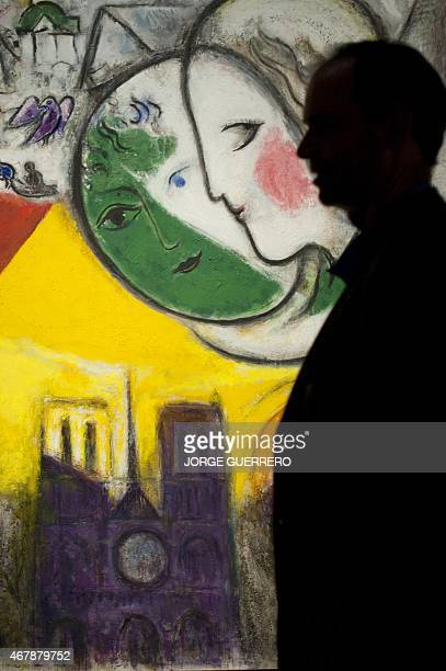 A man walks past a painting by Marc Chagall titled 'Dimanche' during a visit for the press of the Pompidou Art Centre of Malaga in Malaga on March 27...