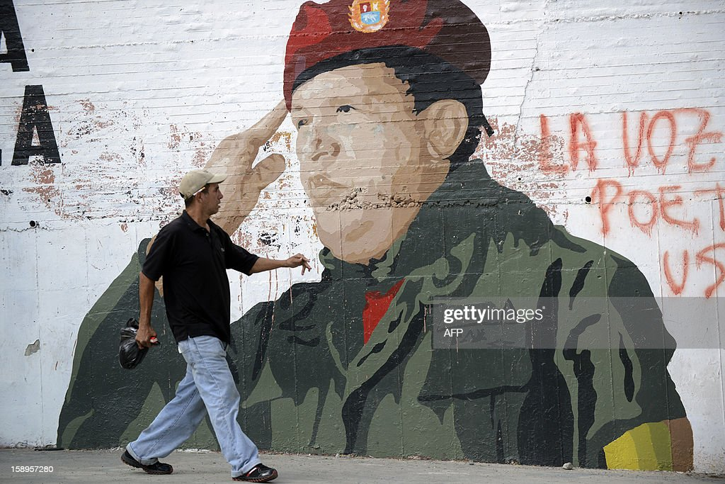 A man walks past a painting of Venezuelan President Hugo Chavez in Caracas on January 4, 2013. Hugo Chavez's top aides have gone on the offensive, accusing the opposition and media of waging a 'psychological war,' as Venezuela's cancer-stricken president battles a serious lung infection. The closing of ranks followed a high-level gathering of top Venezuelan officials in Havana with Chavez, amid growing demands to know whether he will be fit on January 10 to take the oath of office for another six-year-term. AFP PHOTO/Leo Ramirez