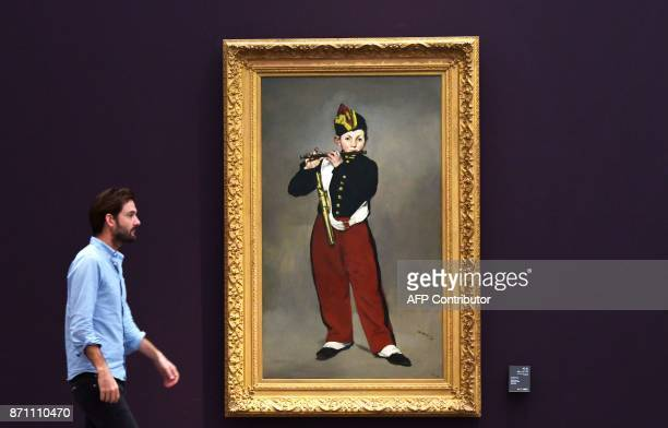 A man walks past a painting titled 'The Fifer' by Edouard Manet inside a gallery of the Louvre Abu Dhabi Museum during a media tour on November 6...