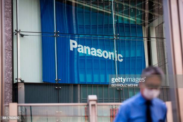 A man walks past a Panasonic building in Tokyo on May 11 2017 Panasonic released its fullyear earnings until end of March 2017 / AFP PHOTO / Behrouz...