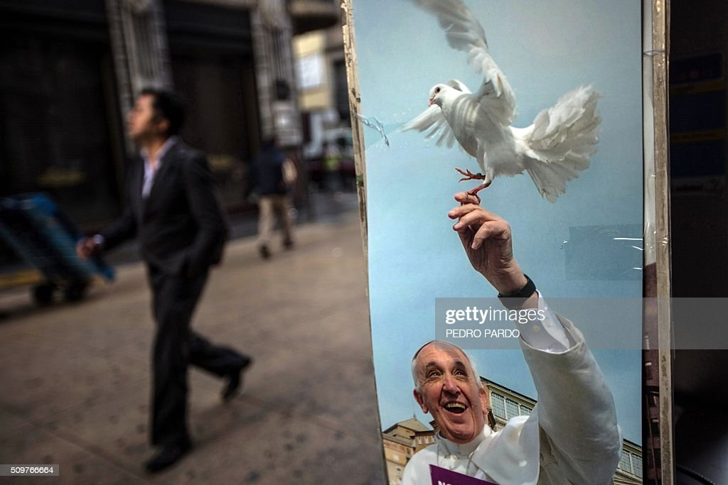 A man walks past a payphone displaying an image of Pope Francis, in Mexico City on February 12, 2016 hours before the arrival of the pontiff to the country. Pope Francis left Rome on Friday bound for Cuba, where he is to hold a historic meeting Russian Patriarch Kirill before continuing on to Mexico for a five-day visit. AFP PHOTO / Pedro PARDO / AFP / Pedro PARDO