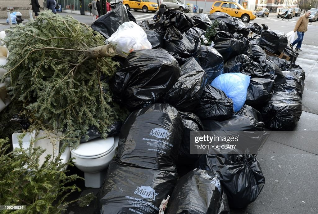 A man walks past a pile of garbage, Christmas trees and broken toilets on the sidewalk on the Upper East Side in New York January 10, 2013. AFP PHOTO / TIMOTHY A. CLARY