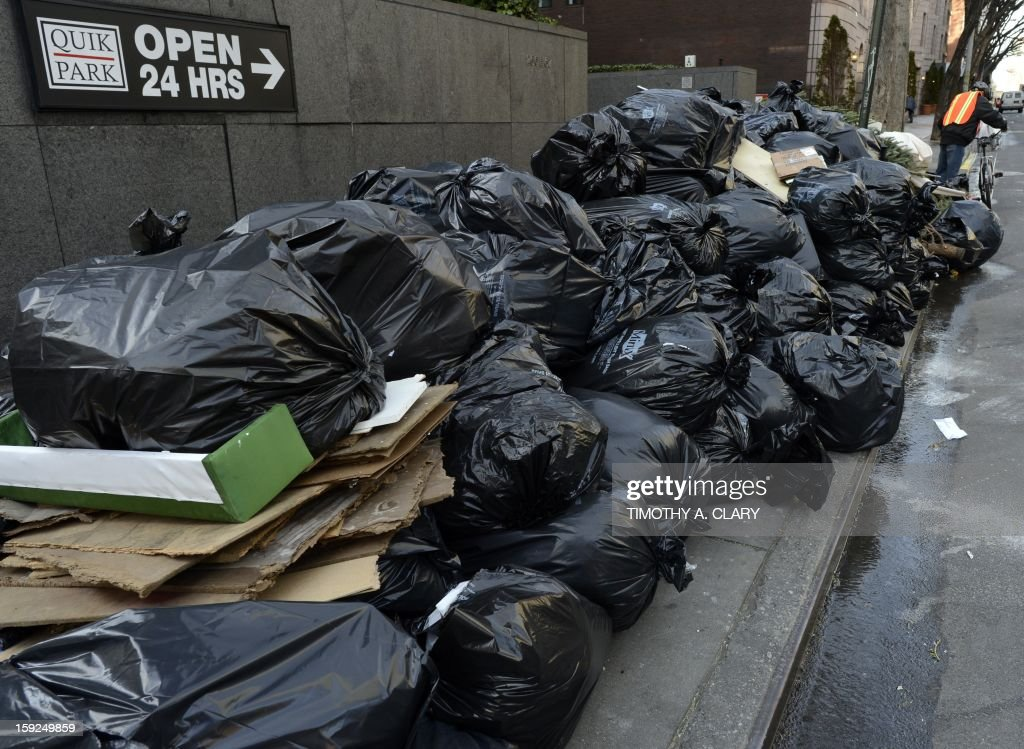 A man walks past a pile of garbage, Christmas trees and broken toilets on the sidewalk on the Upper East Side in New York January 10, 2013.