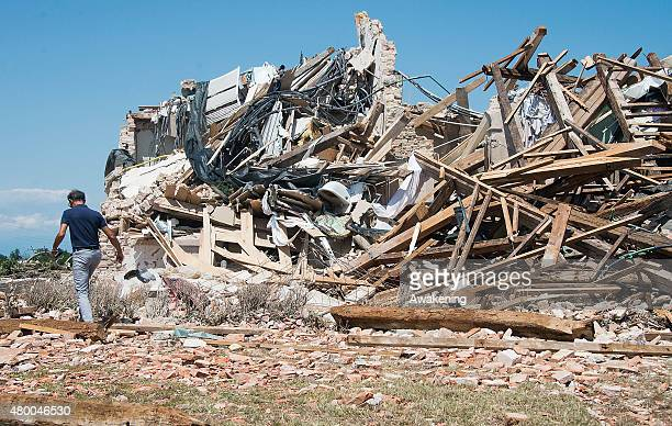 A man walks past a pile of rubbles of wing of Villa Fini destroyed by last night tornado on July 9 2015 in Venice Italy A tornado swept through the...