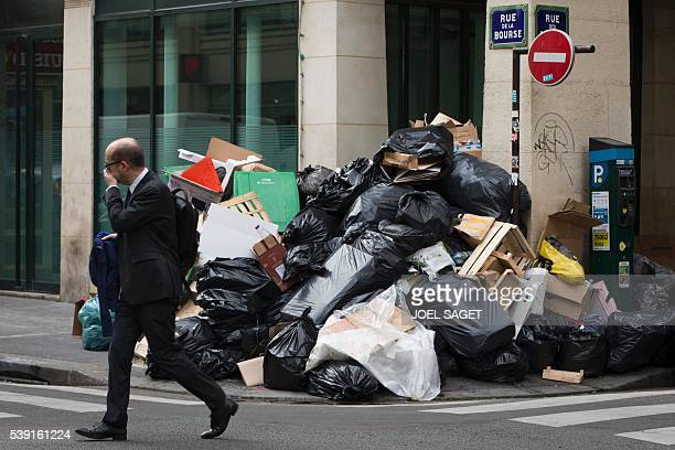 TOPSHOT A man walks past a pile of uncollected rubbish on June 10 2016 in Paris Paris Mayor Anne Hidalgo promised on June 10 2016 that 'all rubbish'...