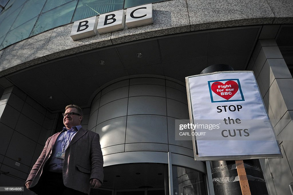 A man walks past a placard outside the BBC White City Media Village in west London on February 18, 2013. Today, February 18, 2013, BBC journalists began a 24-hour strike in protest at compulsory redundancies, causing possible disruption to the broadcaster's television and radio output. Members of the National Union of Journalists (NUJ) walked out at midnight (local time and GMT) at the end of Sunday's programming, over job cuts which are expected to affect BBC Scotland, Five Live, the Asian Network and the World Service. AFP PHOTO / CARL COURT