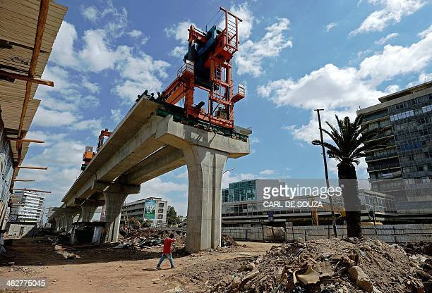 A man walks past a portion of the Addis Ababa light railway under construction in Addis Ababa on January 15 2014 The Addis Ababa Light Railway system...