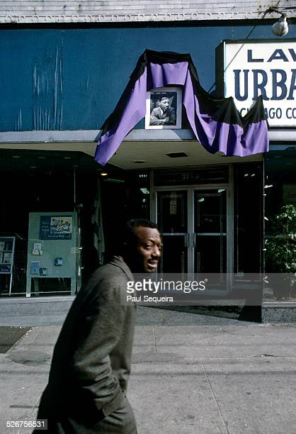 A man walks past a portrait of Martin Luther King Jr wrapped in purple drapery and set above a business' doors in tribute to the recently...