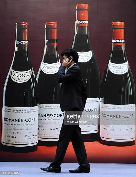 A man walks past a poster advertising fine wines at a Sotheby's auction preview in Hong Kong on March 31 2011 Sotheby's Hong Kong will hold its 2011...