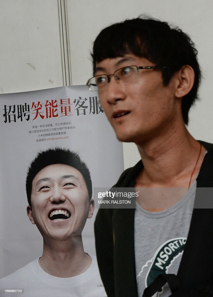 A man walks past a poster as he attends a jobs fair in Beijing on May 18, 2013. Chinese state media has reported that the China will need to find employment for a record number (seven million) of college graduates this year as the country's economy continues to slow. AFP PHOTO / Mark RALSTON