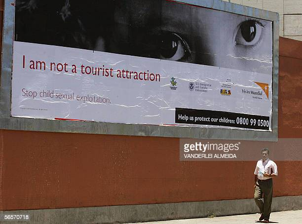 A man walks past a poster of a campaign against child sexual exploitation in Rio de Janiero 11 January 2006 The Brazilian government together with...