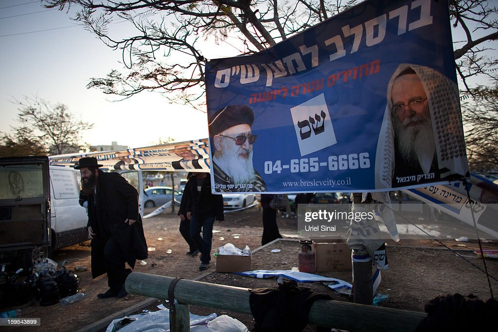 A man walks past a poster of the ultra-Orthodox Shas party ahead of the upcoming Israeli elections during the annual pilgrimage to the grave of Rabbi Baba Sali in the southern Israeli town of Netivot on January 15, 2013 in the southern Israeli town of Netivot, Israel. Thousands of Jews, mainly of Moroccan origin, gathered to pray and hold festivities at the tomb of the respected rabbi who was known as a miracle maker by religious Jews.