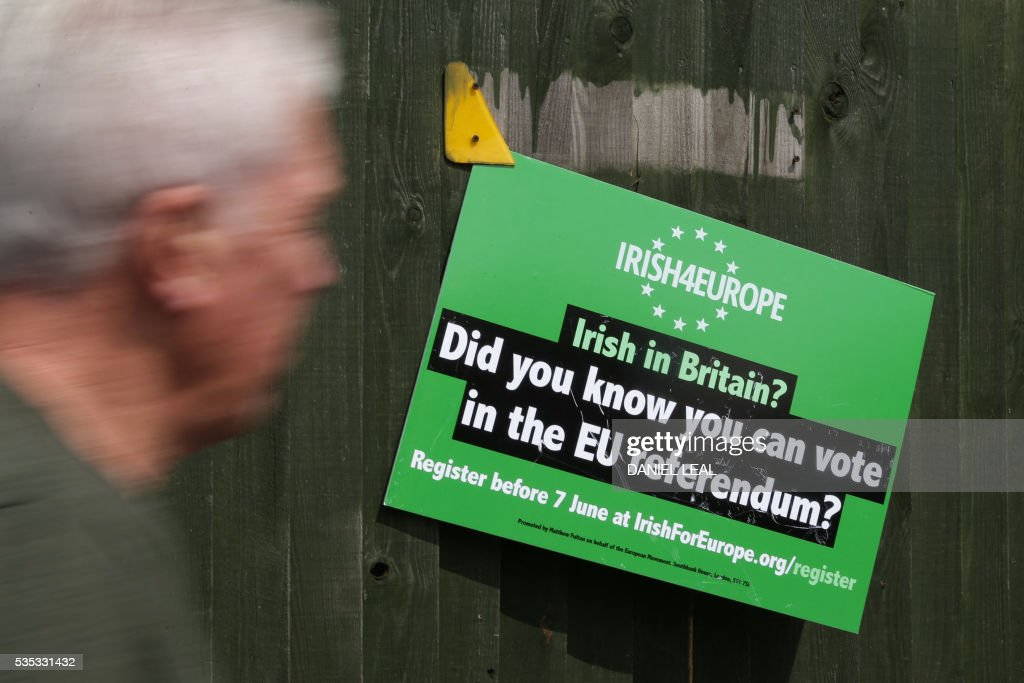 A man walks past a poster put up by activists from the pro-Europe campaign group 'Irish4Europe', an Irish group supporting the 'Remain' campaign for the forthcoming EU referendum, outside the London vs Mayo Gaelic Athletic Association (GAA) football game at Ruislip GAA grounds in Ruislip, northwest London, on May 29, 2016. Irish4Europe is a civic campaign to secure Britains future in the European Union. Activists were leafletting to raise awareness that Irish citizens living in the UK can vote in the EU referendum on June 23, 2016. / AFP / DANIEL